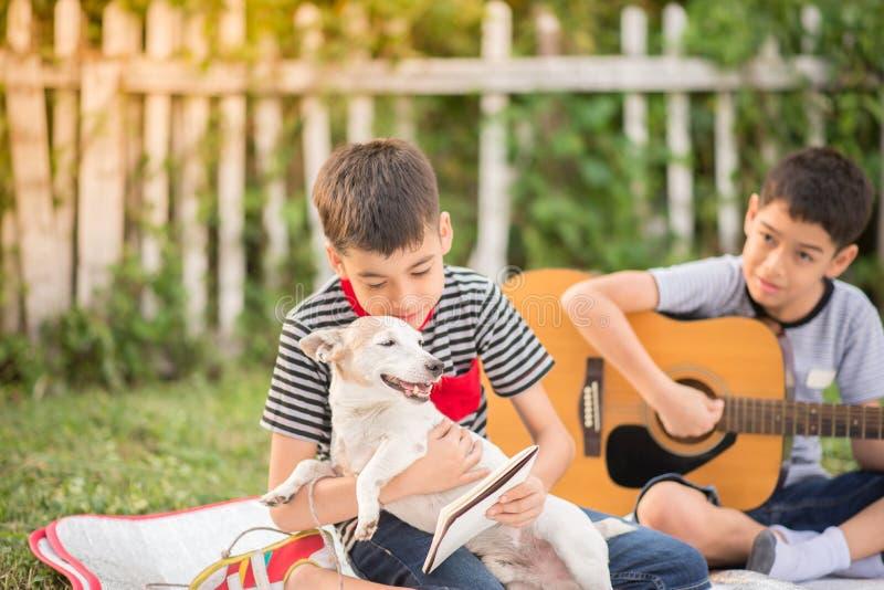 Pojedyncza mama i synowie bawić się gitarę wpólnie w parku zdjęcie royalty free