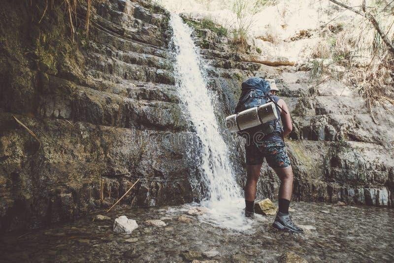 Pojedyncza podróżnicza mężczyzna pozycja blisko Great Falls Shulamit spada w płytkiego staw z szmaragd wodą Ein Gedi - rezerwat p fotografia royalty free