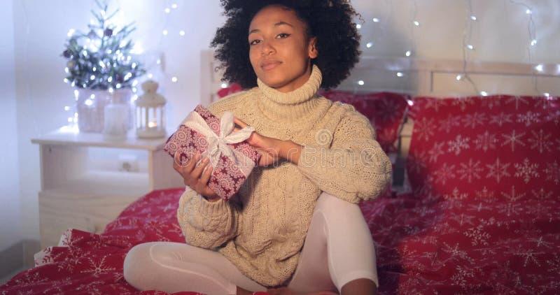 Pojedynczego kobiety mienia Bożenarodzeniowy prezent w łóżku obrazy stock
