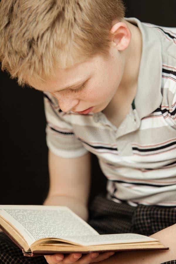 Pojedynczy chłopiec obsiadanie, czytanie i książka zdjęcia stock