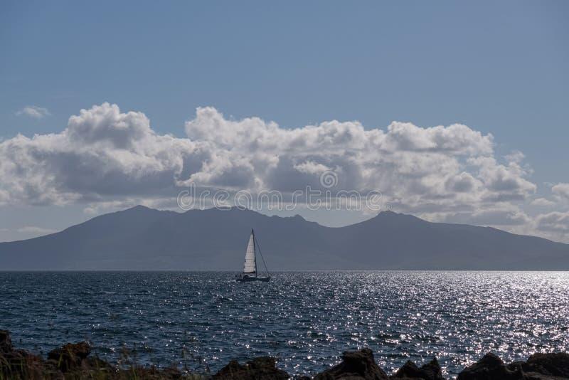 Pojedynczy jacht z białym żagla żeglowaniem przed wyspą Arran na Rzecznym Clyde w Szkocja na lata Solstice zdjęcie royalty free