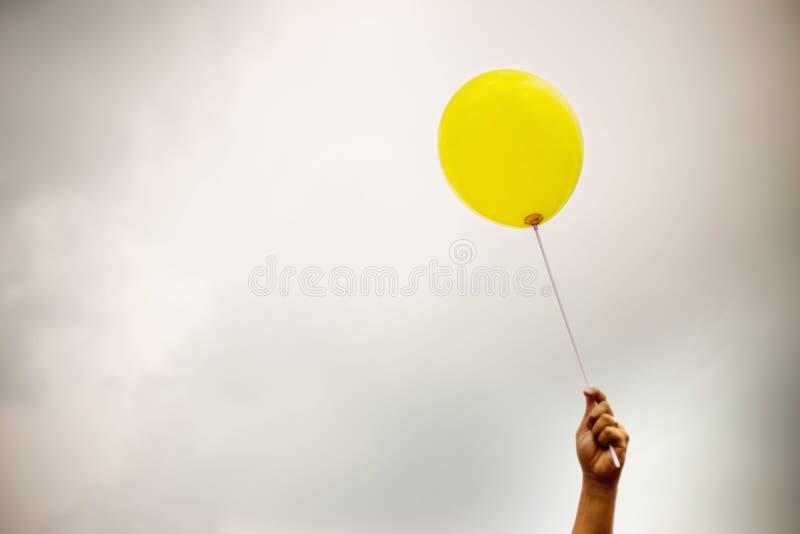 Pojedynczy koloru żółtego balon pod chmurnym niebem ręka trzyma balonową arkanę do nieba fotografia royalty free