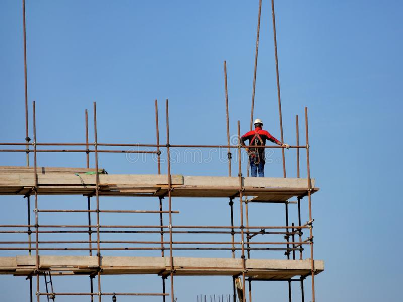Pojedynczy pracownik budowlany na budowy rusztowaniu obrazy royalty free
