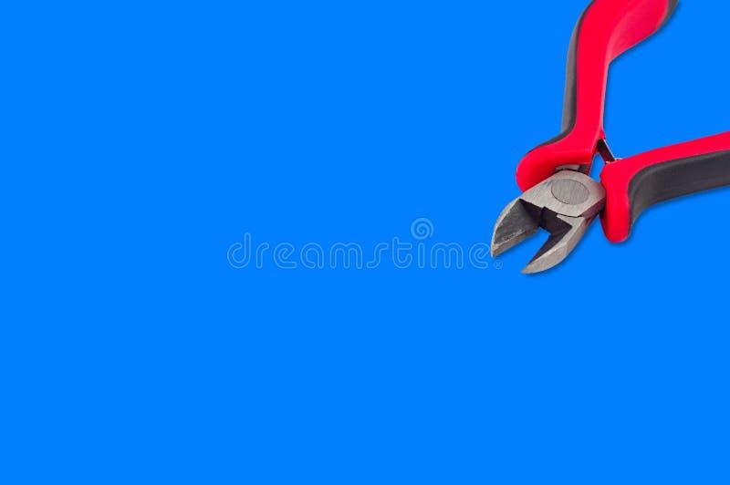 Pojkar för att klippa tråd med röda och svarta plast- eller gummihandtag på blå bakgrund royaltyfria bilder