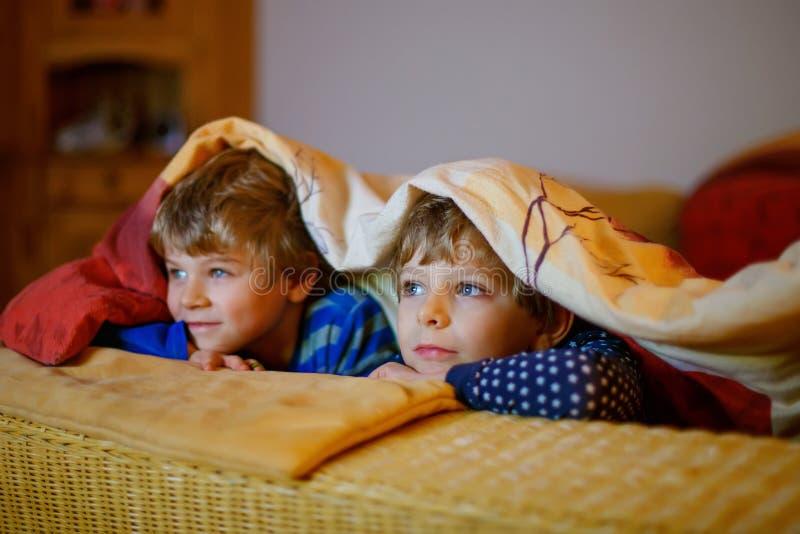 Pojkar för liten unge som håller ögonen på television och tycker om tecknade filmer arkivfoto