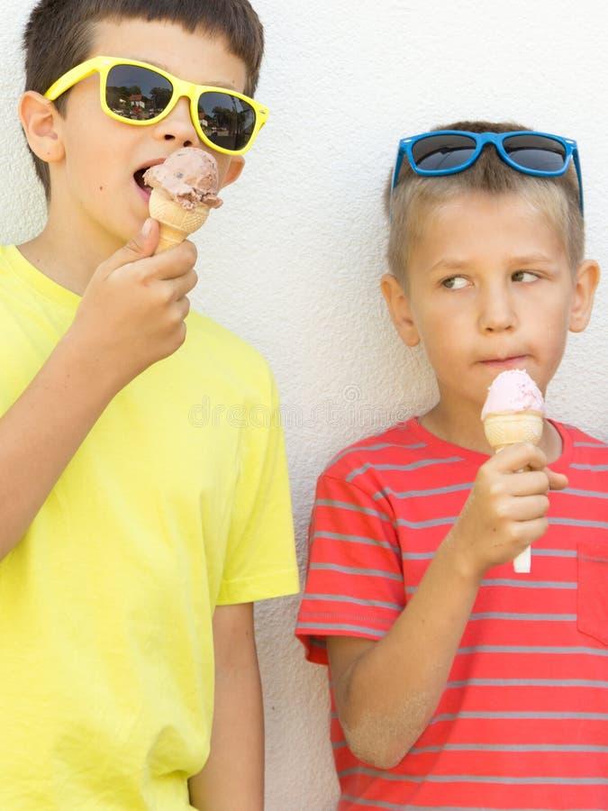 Pojkar för unga ungar som äter glass arkivfoton