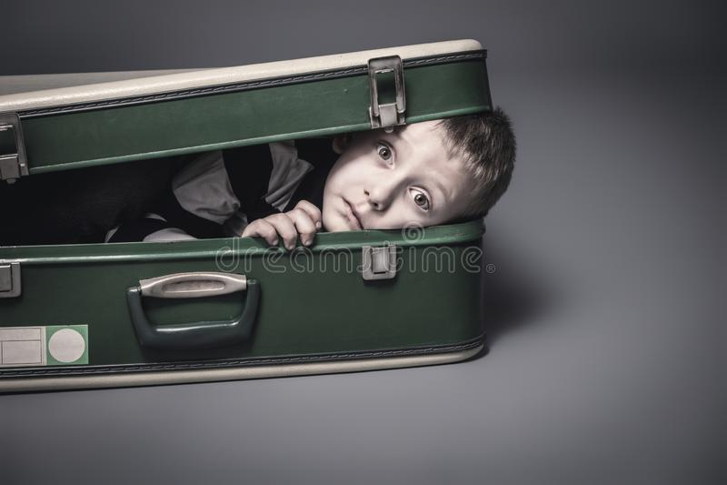 Pojkar gömmer sig i en gammal resväska royaltyfri foto