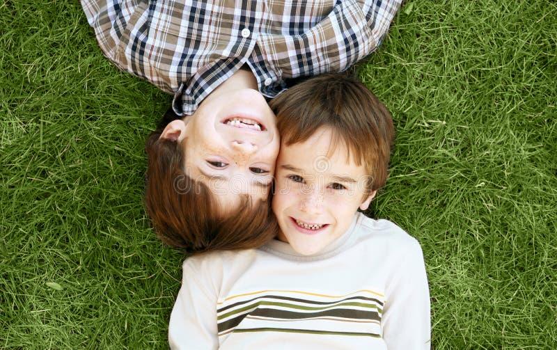 pojkar gräs läggande arkivfoton