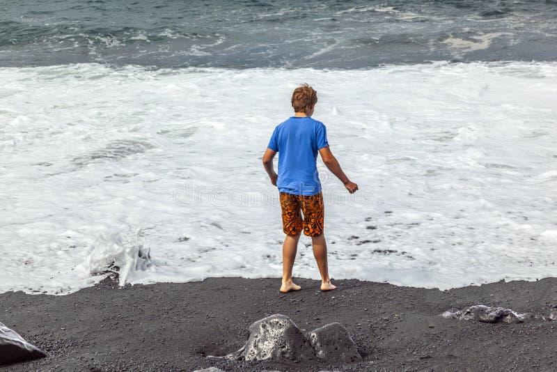 Download Pojkar Har Gyckel På Den Svarta Stranden Arkivfoto - Bild av nätt, ferie: 37344642