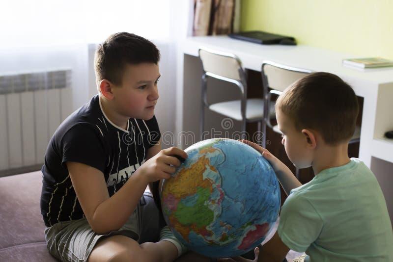Pojkar med jordklotet tänker var att gå på semester royaltyfria bilder