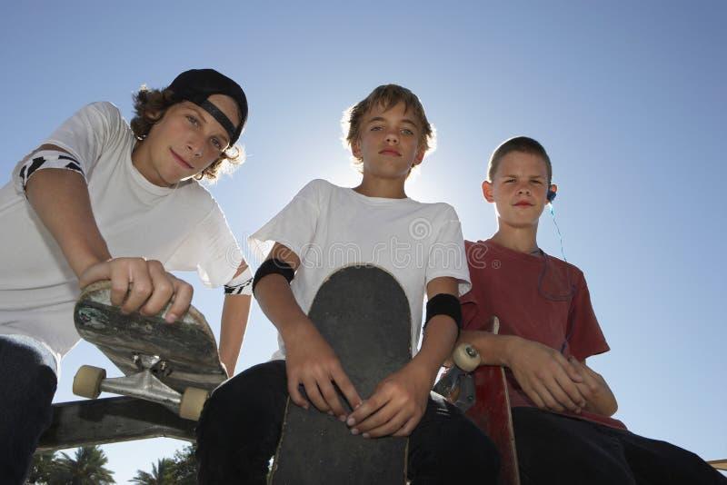 Pojkar med skateboarder mot blå himmel royaltyfri bild