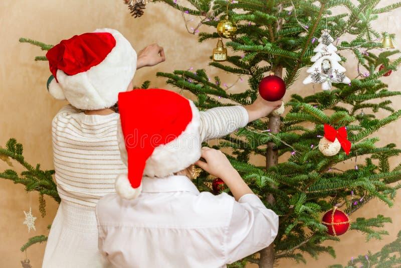 Pojkar och flickan dekorerar julträdet arkivbild