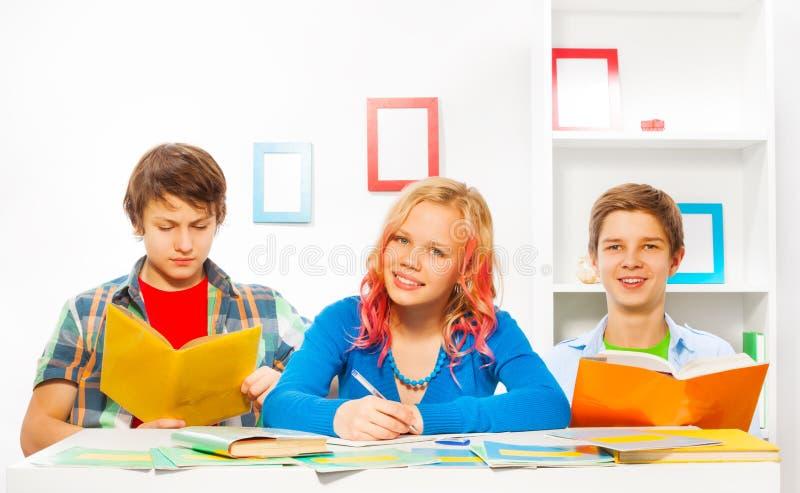Pojkar och flickan gör läxa tillsammans hemma arkivfoto