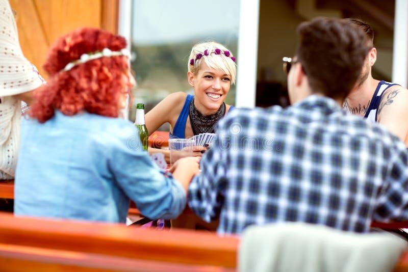 Pojkar och flickor har gyckel medan spela kort i den utomhus- restaurangen royaltyfria foton