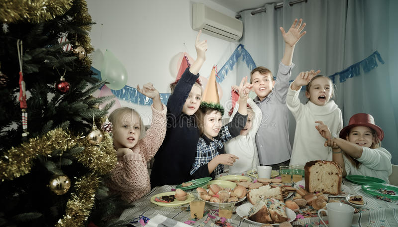 Pojkar och flickor som jokingly uppför under friend'sfödelsedagdelen arkivfoto