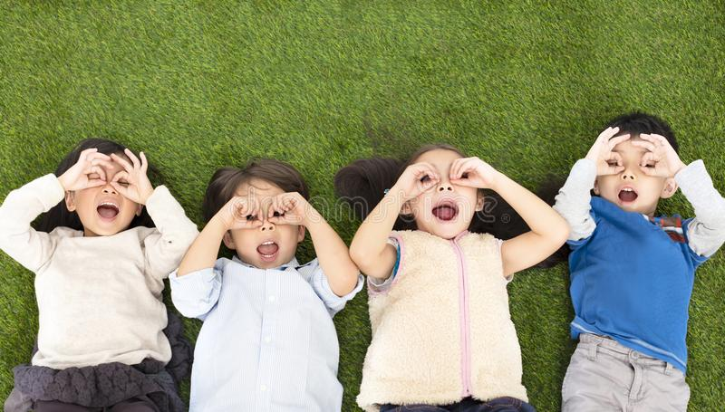 Pojkar och flickor som ligger på grönt gräs royaltyfria foton