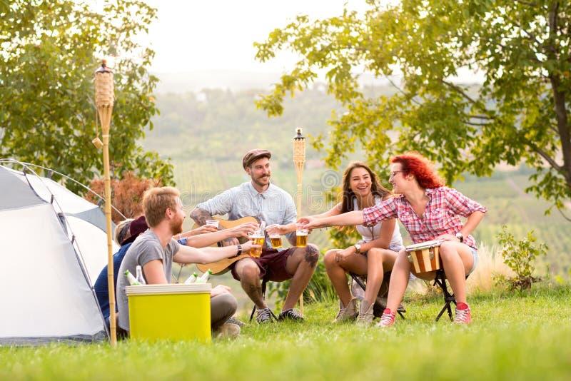 Pojkar och flickor som rostar med öl i campgroung royaltyfri bild