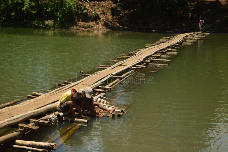 Pojkar på en tillfällig sväva bro royaltyfria foton