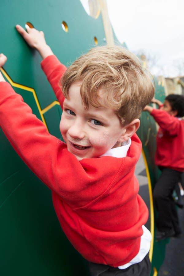 Pojkar på klättringväggen i skolalekplats på Breaktime arkivfoton