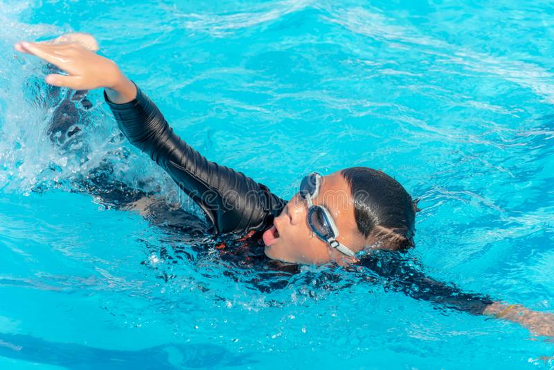 Pojkar simmar i pölen royaltyfri fotografi