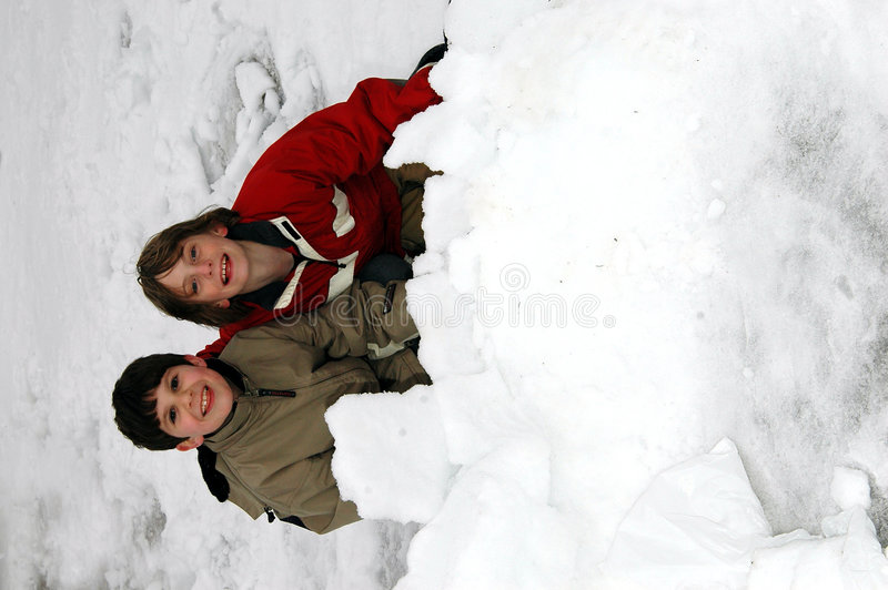 pojkar som bygger iglooen arkivbild