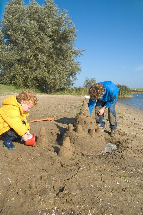 pojkar som bygger sandcastlen royaltyfri fotografi