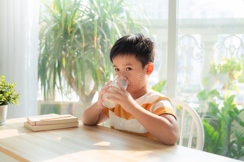 Pojkar som dricker mjölk, kalciumföda för hälsosam kropp och hjärnutveckling arkivfoto