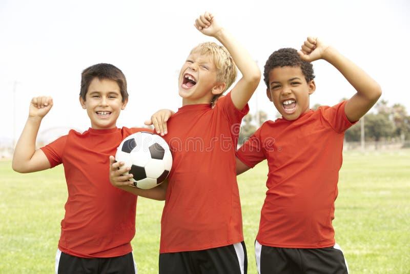 pojkar som firar fotbollslagbarn fotografering för bildbyråer