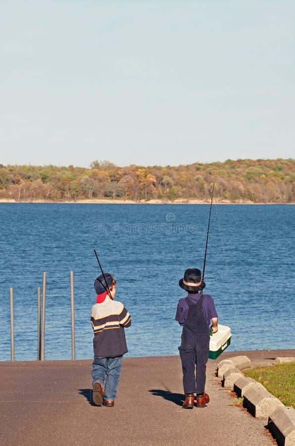 pojkar som fiskar att gå royaltyfria foton