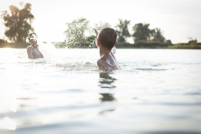 Pojkar som har gyckel i en sjö royaltyfria foton