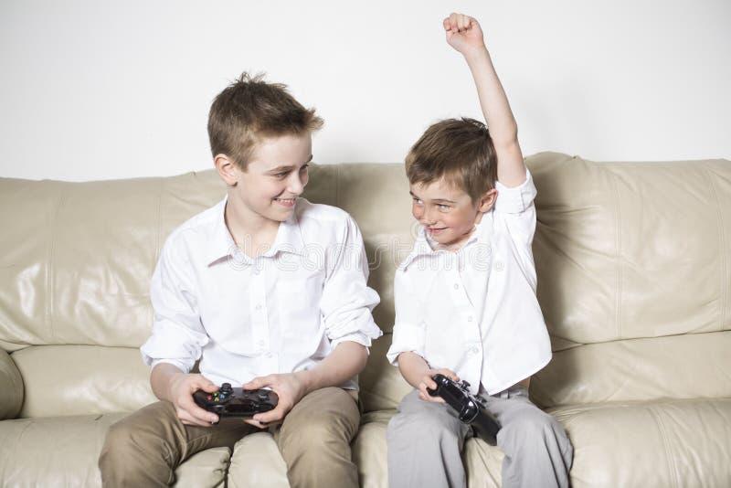 Pojkar som har massor av gyckel med videospel royaltyfria bilder