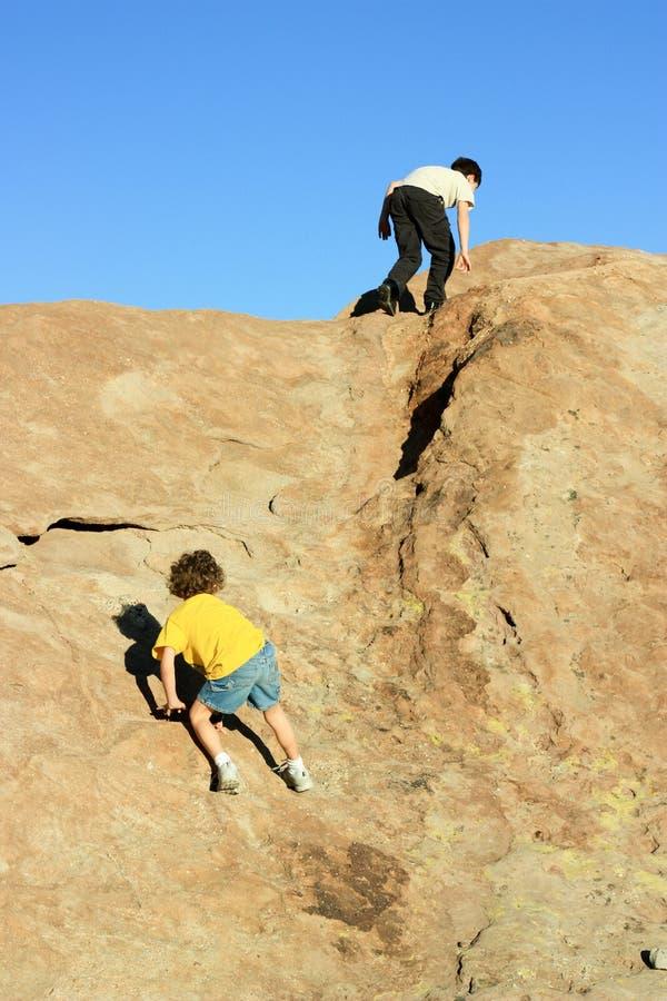 pojkar som klättrar rocks arkivfoton