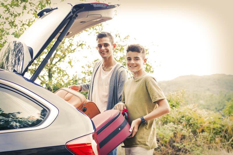 Pojkar som laddar bilkängan för ferier fotografering för bildbyråer