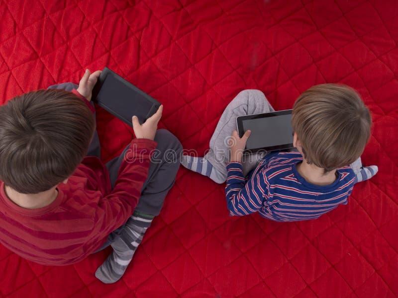 Pojkar som leker lekar på tabletdatorer royaltyfria foton