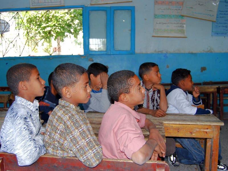 Pojkar som sitter på deras skivor på skolan i Egypten arkivfoto