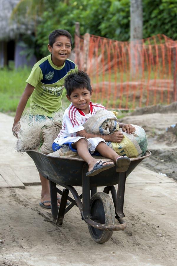 Pojkar som skjuter en hjulkärra på Indiana i Peru arkivfoto