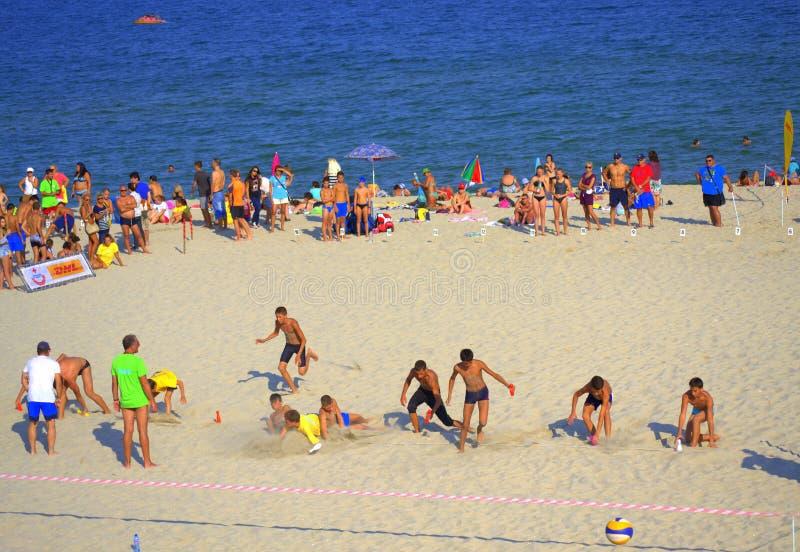 Pojkar som snappar sista ben på strandkörningen royaltyfri foto