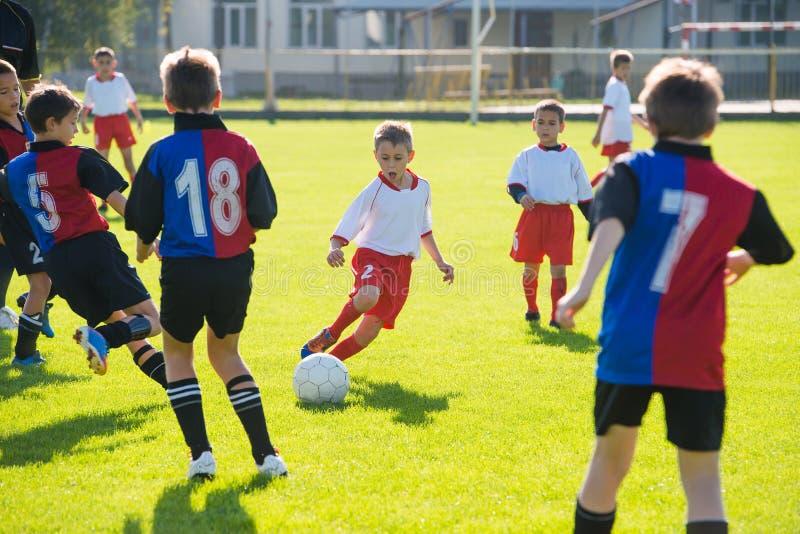 Pojkar som sparkar fotboll arkivfoto