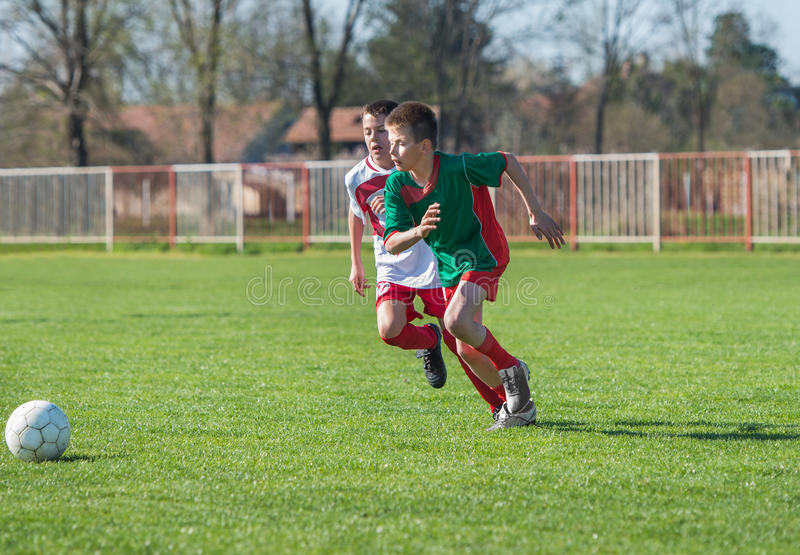 Pojkar som sparkar fotboll fotografering för bildbyråer