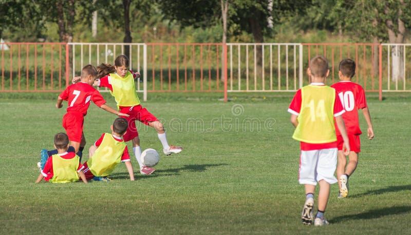 Pojkar som sparkar fotboll arkivbild