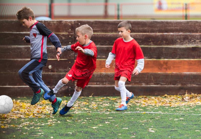 Pojkar som sparkar fotboll arkivbilder