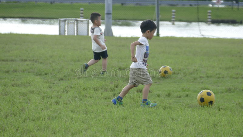 Pojkar som sparkar fotboll på sportfältet arkivfoto