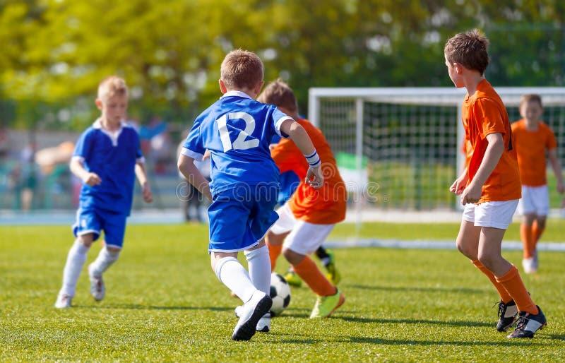 Pojkar som sparkar fotbollleken Unga fotbollsspelare som spelar matchen för ungdomfotbollturnering royaltyfria bilder