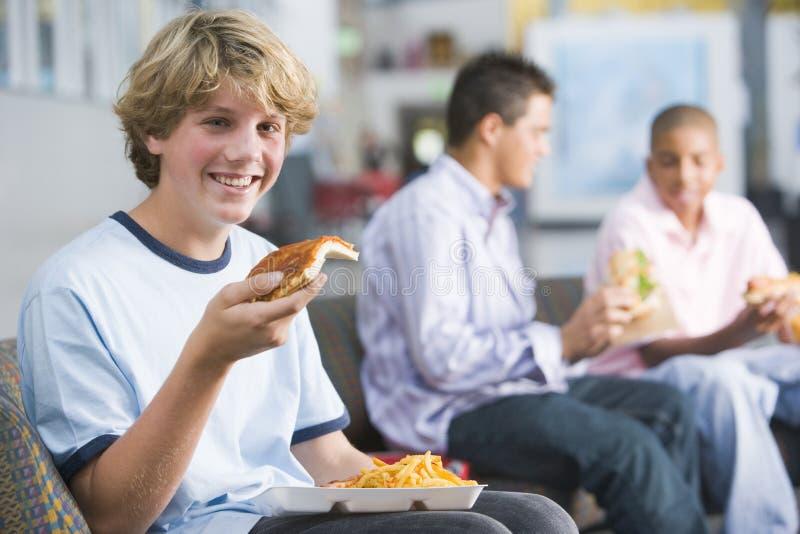 pojkar som tycker om snabbmat, äter lunch tonårs- tillsammans royaltyfria bilder