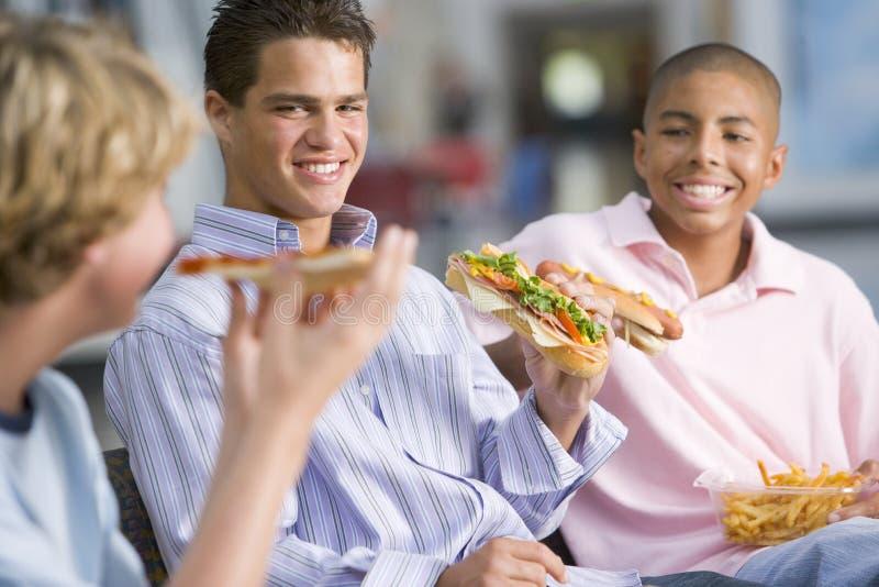 pojkar som tycker om snabbmat, äter lunch tonårs- tillsammans arkivbilder