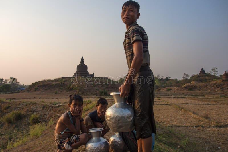 Pojkar väntade för att bära vattenkrukan tillbaka hem med templet som bakgrund royaltyfri foto