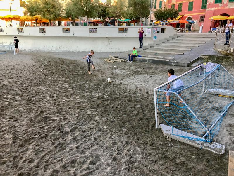 Pojkeövningsfotboll på den Vernazza stranden Cinque Terre, Italien royaltyfri bild
