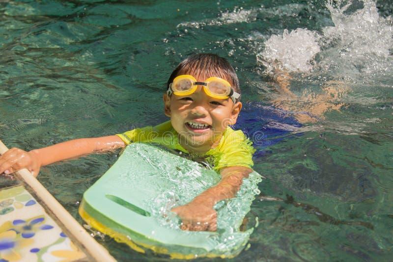 Pojkeövningssimning simning för aktivitetsbarnpöl arkivbild
