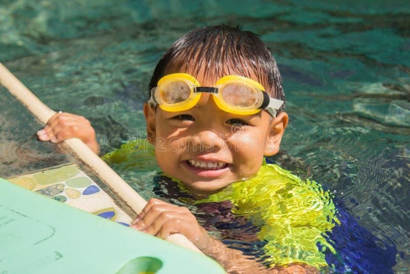 Pojkeövningssimning simning för aktivitetsbarnpöl fotografering för bildbyråer