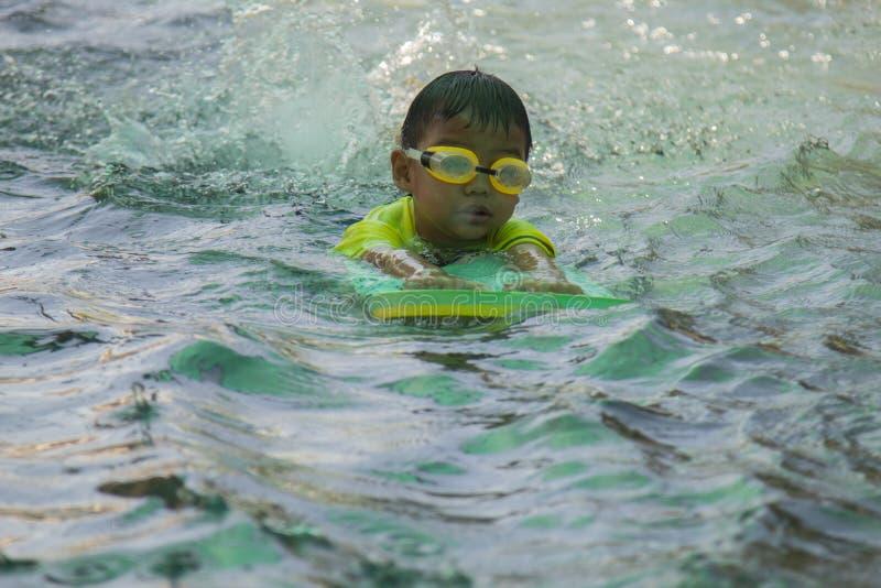 Pojkeövningssimning simning för aktivitetsbarnpöl arkivfoto